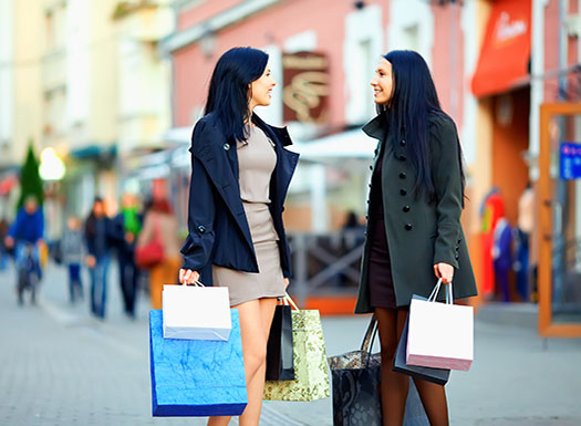 Two ladies shopping on busy street